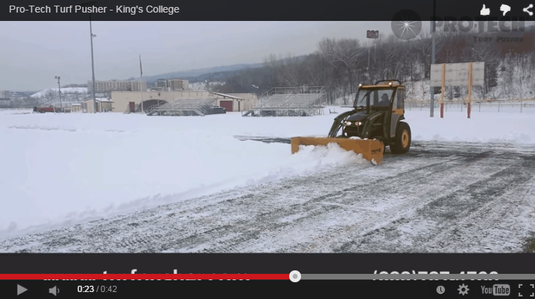 Turf Pusher Clearing Snow on Field